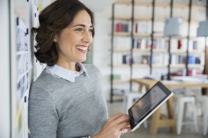 Smiling architect holding digital tablet in office